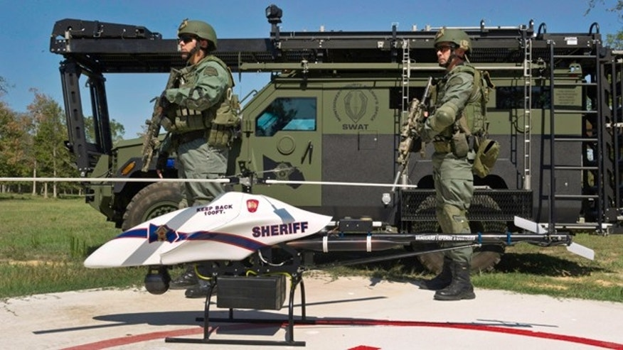 This Sept. 2011 photo provided by Vanguard Defense Industries, shows a ShadowHawk drone with Montgomery County, Texas, SWAT team members.