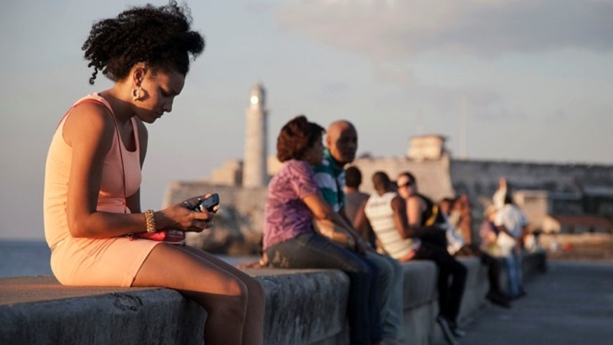 "In this March 11, 2014 photo, a woman uses her cellphone as she sits on the Malecon in Havana, Cuba. The U.S. Agency for International Development masterminded the creation of a ""Cuban Twitter,"" a communications network designed to undermine the communist government in Cuba, built with secret shell companies and financed through foreign banks, The Associated Press has learned. The project, which lasted more than two years and drew tens of thousands of subscribers, sought to evade Cubas stranglehold on the Internet with a primitive social media platform. (AP Photo/Franklin Reyes)"