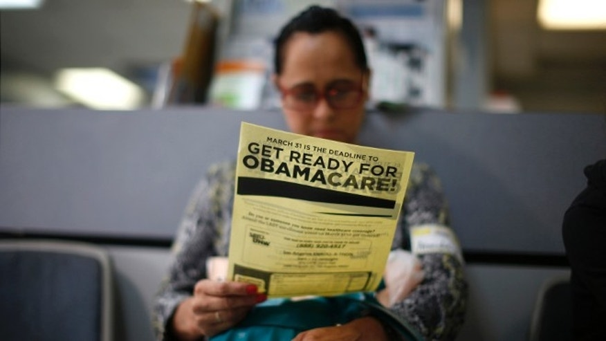 FILE: March 27, 2014: A woman reads a leaflet at a ObamaCare enrollment event in Cudahy, California