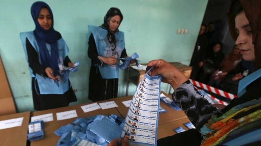 April 5, 2014: Election officials hold paper ballots during the presidential  vote counting process at a polling station in Herat Province, Afghanistan.