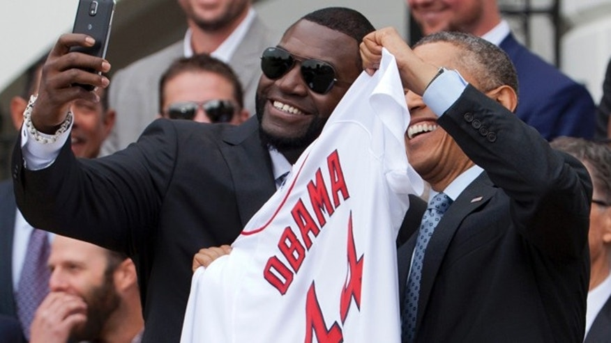 "April 1, 2014: Boston Red Sox designated hitter David  ""Big Papi"" Ortiz, left, takes a selfie with President Obama, holding a Boston Red Sox jersey presented to the president during a ceremony on the South Lawn of the White House."