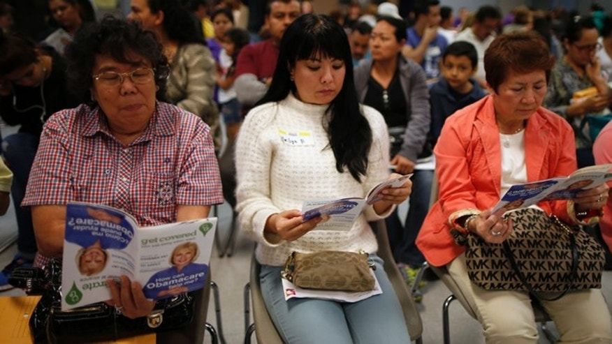 March 27, 2014: People wait in line at a health insurance enrollment event in Cudahy, Calif.
