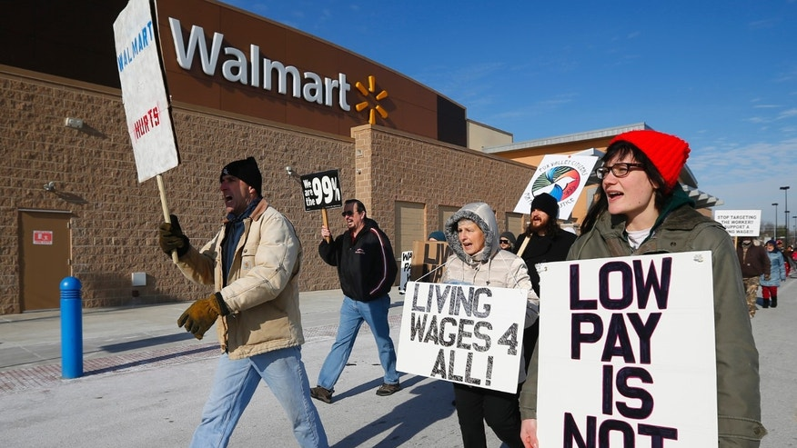 Nov. 29, 2013: A group of protesters walk through the Walmart retail store parking lot on Black Friday in Elgin, Illinois.
