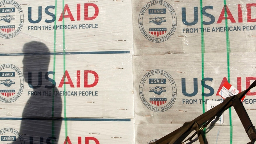 A shadow is cast on boxes of relief items from U.S. Agency for International Development (USAID).