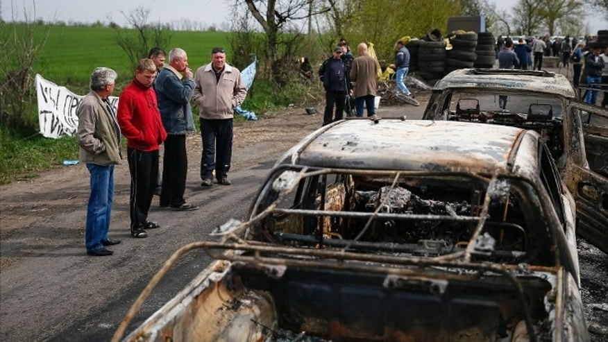 April 20, 2014: Residents look at burnt cars near a checkpoint that was the scene of a gunfight overnight near the city of Slaviansk, Ukraine.
