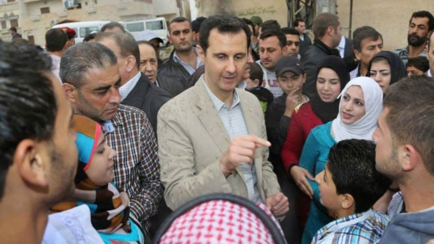 In this photo taken April 20, 2014 and released by the Syrian official news agency SANA, Syrian President Bashar Assad, center, speaks with Syrian citizens during his visit to Ain al-Tineh village, near Damascus, Syria.