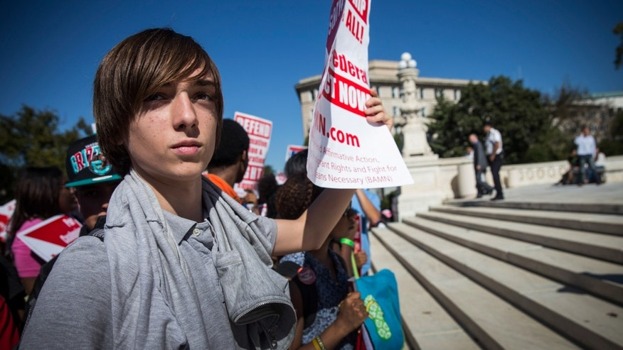 "WASHINGTON, DC - OCTOBER 15:  A boy protests in support of affirmative action, outside the Supreme Court during the hearing of ""Schuette v. Coalition to Defend Affirmative Action"" on October 15, 2013 in Washington, DC. The case revolves around affirmative action and whether or not states have the right to ban schools from using race as a consideration in school admissions.  (Photo by Andrew Burton/Getty Images)"