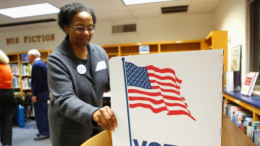 Nov. 5, 2013: An election worker sets up a voting booth in the library of Spring Hill Elementary School, which is being used as a polling station in McLean, Virginia.