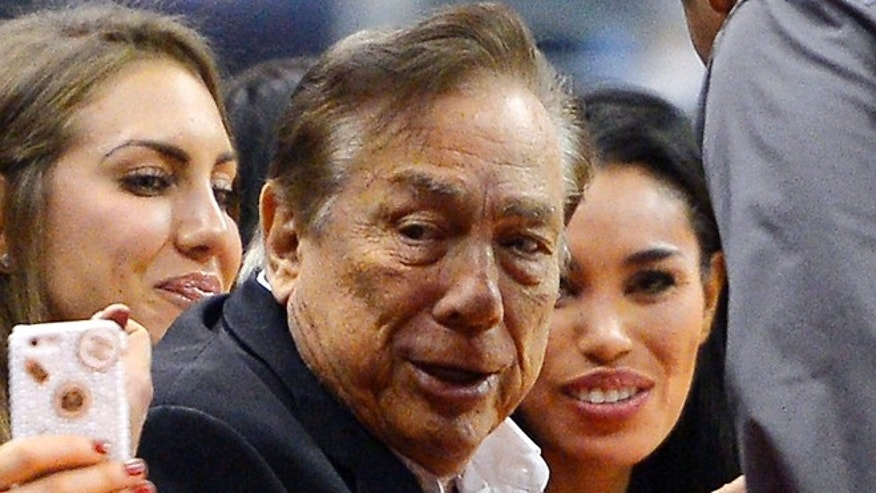 Oct. 25, 2013: In this photo taken, Los Angeles Clippers owner Donald Sterling, center, and V. Stiviano, right, watch the Clippers play the Sacramento Kings during the first half of an NBA basketball game, in Los Angeles.