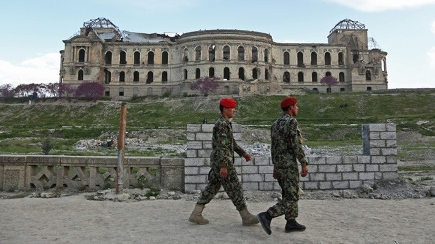 April 27, 2014: Afghan national army soldiers walk past the palace of the late King Amanullah Khan, which was destroyed during the civil war of the early 1990s, in Kabul. (AP Photo/Rahmat Gul)