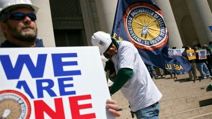 FILE: Members of the International Brotherhood of Electrical Workers join other union workers and supporters during a rally in Oklahoma.