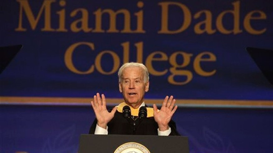 "Vice President Joe Biden, center, speaks during a graduation ceremony at the Miami Dade College in Miami, Saturday, May 3, 2014.  Biden said a ""constant, substantial stream of immigrants"" is important to the American economy, urging citizenship for immigrants living in the U.S. illegally.   (AP Photo/Javier Galeano)"
