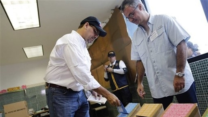 Jose Domingo Arias, left, presidential candidate for the Democratic Change Party, casts his ballots at a polling station in Panama City, Sunday, May 4, 2014. Panamanians are choosing President Ricardo Martinelli's successor in a three-way dogfight marked more by ugly personality clashes than any deep disagreements over the way forward for Latin America's standout economy. (AP Photo/Tito Herrera)