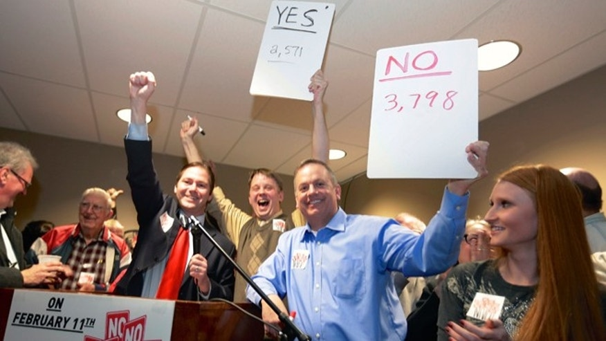FILE - In this file photo from Feb. 11, 2014, State Sen. Charlie Jansssen of Fremont, third left, Jeremy Jensen, center, and John Wiegert, second right, celebrate in Fremont, Neb., after city voters have decided by voting no, to uphold the law designed to bar immigrants from renting homes if they dont have legal permission to be in the U.S.  On Monday, May 5, 2014, the U.S. Supreme Court decided not to review Fremont's ordinance that bans renting homes to immigrants living in the country illegally. Supporters of the ordinance said it could open the door to similar laws elsewhere. (AP Photo/Nati Harnik, File)