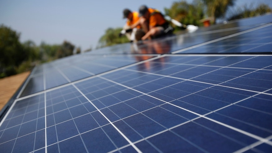 FILE: Solar technicians install solar panels on the roof of a house in Mission Viejo, California.