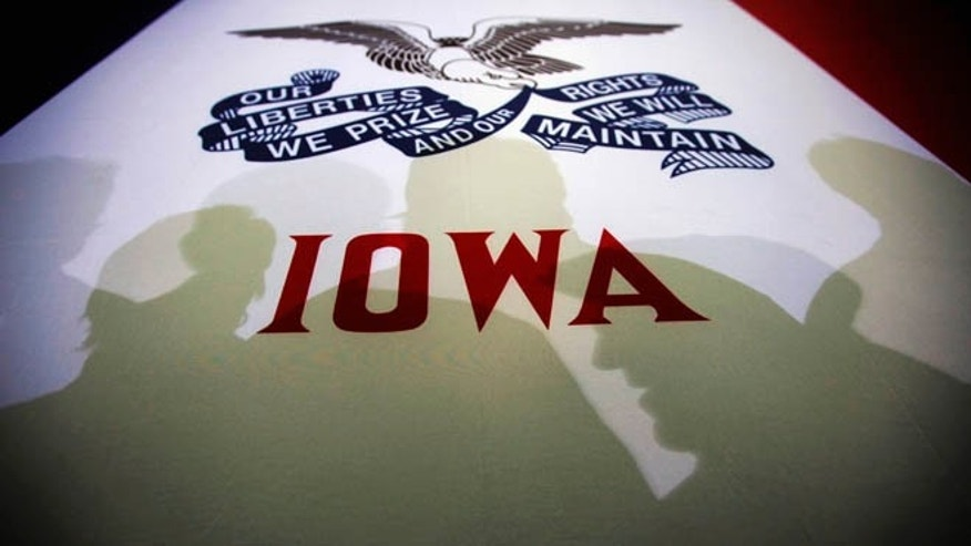 FILE: January 2, 2012: Potential caucus voters cast shadows on an Iowa state flag at a GOP campaign rally, Clive, Iowa.