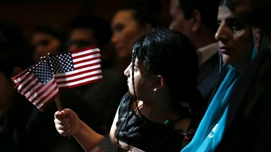 Sunlight peeking through a window at the Jersey City City Hall shines 5-year-old Anmol Sajid as she waves U.S. flags during a naturalization ceremony in which her mother, Uzma Gulzar, right, of Pakistan, was sworn in as United States citizen, Friday, April 25, 2014, in Jersey City, N.J. The U.S. Citizenship and Immigration Services claims the ceremony is the first- ever held at Jersey City City Hall. (AP Photo/Julio Cortez)