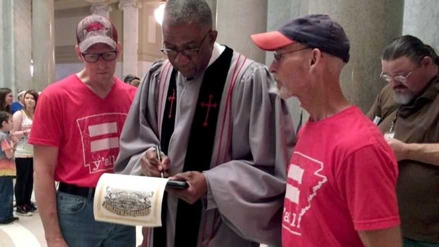 May 12, 2014: After marrying Allan Cox, 48, left, and Steve Thomas, 61, right, Judge Wendell Griffen, center, signs their marriage license in this photo in Little Rock, Ark.