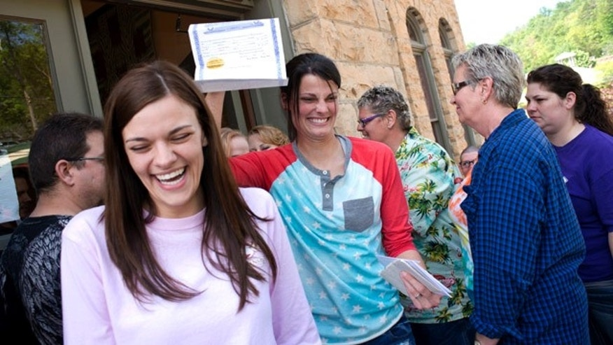 May 10, 2014: Kristin Seaton, center, of Jacksonville, Ark., holds up her marriage license as she leaves the Carroll County Courthouse in Eureka Springs, Ark., with her partner, Jennifer Rambo, left, of Fort Smith, Ark., in Eureka Springs, Ark. (AP Photo/Sarah Bentham, file)