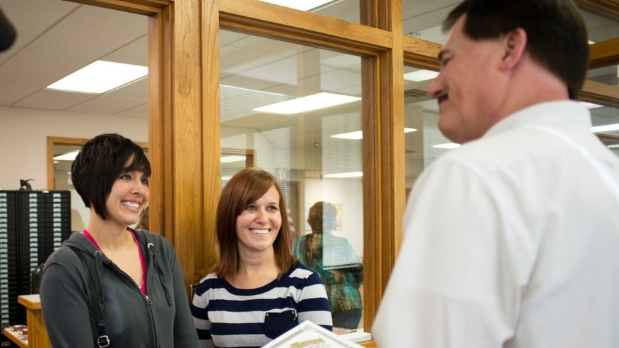 May 16, 2014: Beth Moore, left, and her partner Abby Hill, center, exchange vows in a marriage ceremony performed by Jeremy Hernandez, right, at the Washington County Courthouse in Fayetteville, Ark.