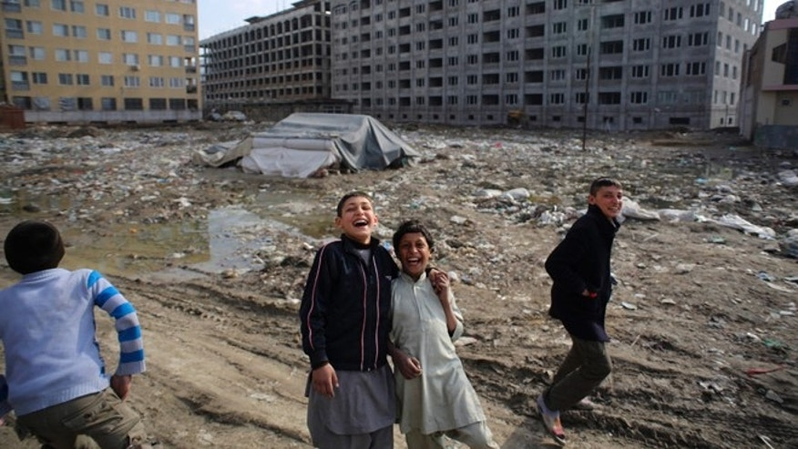 FILE: Afghan boys play near a residential complex which is under construction in Kabul.
