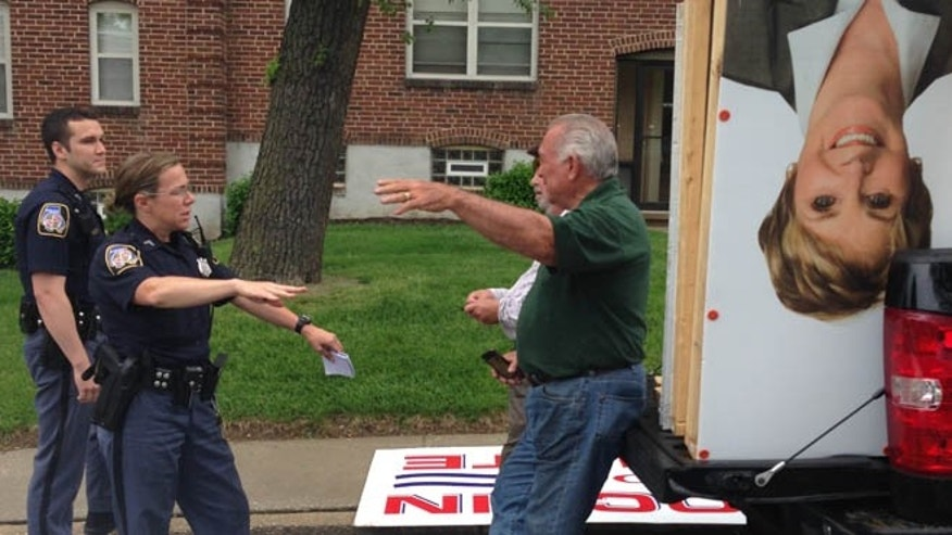 May 10, 2014: J. Ronald DeJuliis, a commissioner for Maryland Democratic Gov. Martin O'Malley talks to police about campaign signs, Balto., Md.
