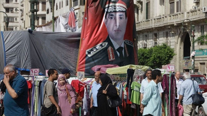 May 17, 2014: Egyptians walk past a banner with a portrait of Egyptian Presidential hopeful Abdel-Fattah el-Sissi at a market in Cairo, Egypt.