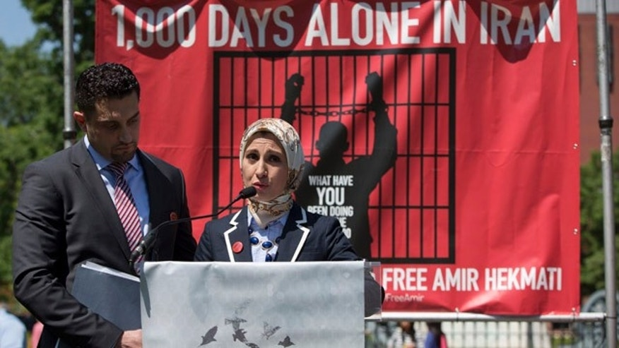 May 19, 2014: Ramy Kurdi listens as left, as his wife Sarah Hekmati, sister of Amir Hekmati, a former Marine from Michigan incarcerated in Iran since 2011, speaks in Lafayette Park across the street from the White House in Washington during a gathering of family members and supporters calling for his freedom. (AP Photo/Carolyn Kaster)