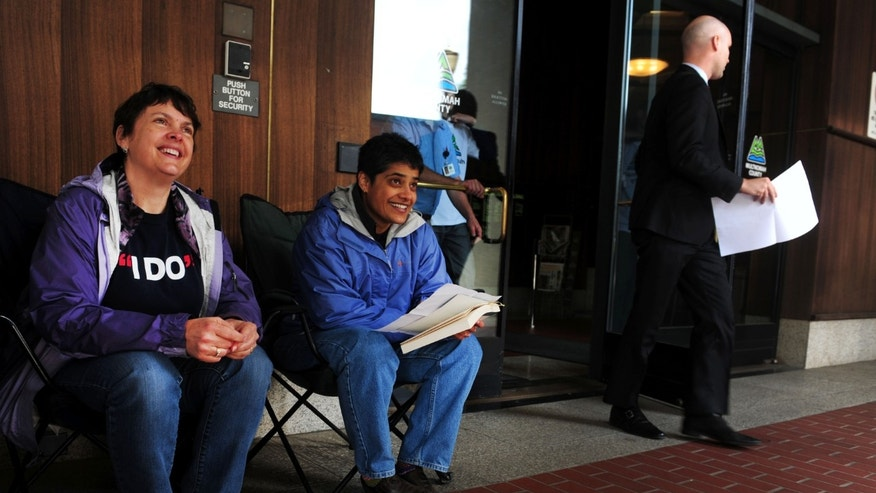May 19, 2014: Laurel Gregory, left, and Shilpi Benerjee pass the time waiting for a ruling in front of the Multnomah County Recorder's building in Portland, Ore.