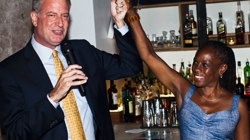 Then-New York City mayoral candidate Bill de Blasio holds up the hand of his wife Chirlane McCray at a campaign event.