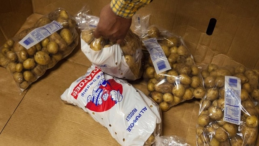 Clients take bags of potatoes at the St. Vincent de Paul food pantry in Indianapolis, Indiana.