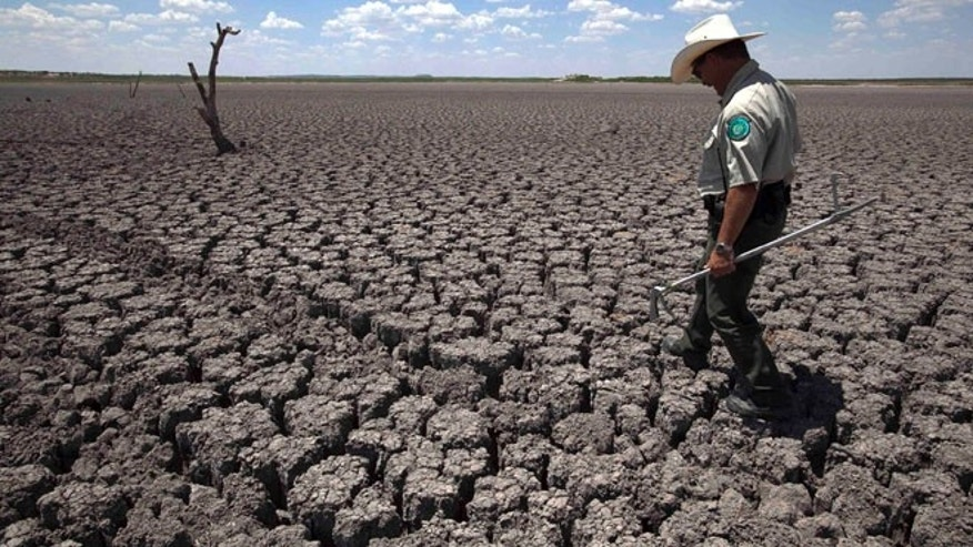 Aug. 3, 2011, file photo of Texas State Park police officer Thomas Bigham walking the cracked lake bed of O.C. Fisher Lake in San Angelo, Texas.