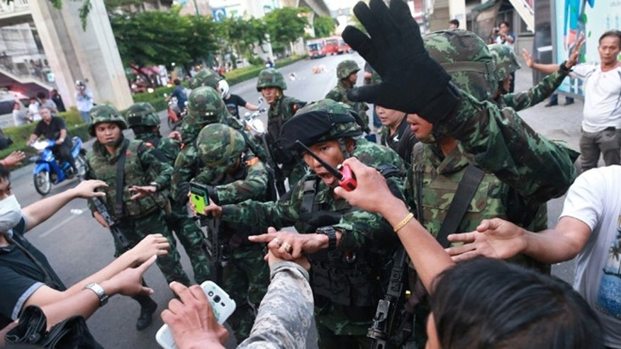 May 24, 2014: Thai soldiers scuffle with protesters during an anti-coup demonstration at the Victory Monument in Bangkok, Thailand.