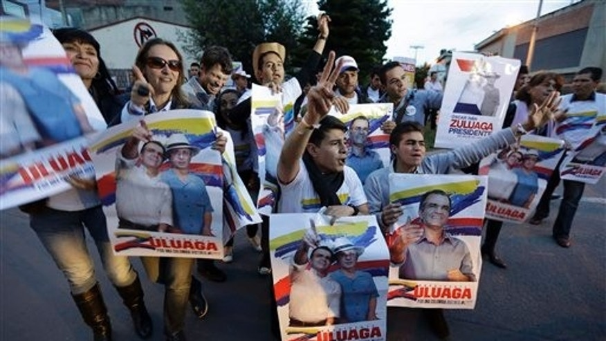 Supporters of Oscar Ivan Zuluaga, candidate for the Democratic Center, chant slogans outside the a TV station prior to a televised presidential debate in Bogota, Colombia, Thursday, May 22, 2014. Colombia will hold presidential election on May 25.  (AP Photo/Fernando Vergara)