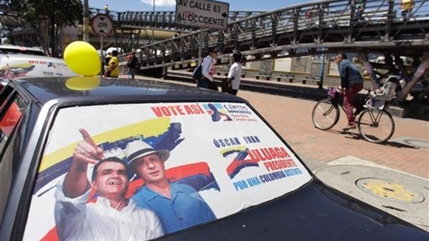 A campaign poster on the back of a car car window promotes Democratic Center Party presidential candidate Oscar Ivan Zuluaga, who is pictured with former President Alvaro Uribe, in Bogota, Colombia, Saturday, May 24, 2014. Polls say that Zuluaga is running neck and neck with Colombia's President and Social Party of National Unity presidential candidate, Juan Manuel Santos, well ahead of three other candidates but neither likely to garner the 50 percent in the May 25th election, needed to avoid a runoff. (AP Photo/Javier Galeano)