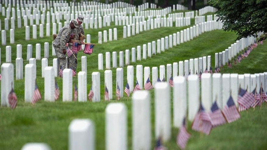 May 22, 2014: Soldiers of the 3rd U.S. Infantry Regiment place flags at grave sites at Arlington National Cemetery in Arlington, Va.