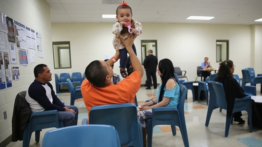 ADELANTO, CA - NOVEMBER 15: An immigrant detainee holds his daughter during a family visitation visit at the Adelanto Detention Facility on November 15, 2013 in Adelanto, California. The facility, the largest and newest Immigration and Customs Enforcement (ICE), detention center in California, houses an average of 1,100 immigrants in custody pending a decision in their immigration cases or awaiting deportation. The average stay for a detainee is 29 days. The facility is managed by the private GEO Group. ICE detains an average of 33,000 undocumented immigrants in more than 400 facilities nationwide. (Photo by John Moore/Getty Images)