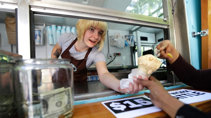 June 2, 2014: Caitlyn Faircloth, a worker with Molly Moon's Homemade Ice Cream, hands out free ice cream next to a tip jar at a rally celebrating the passage of a $15 minimum wage measure outside Seattle City Hall in Seattle.