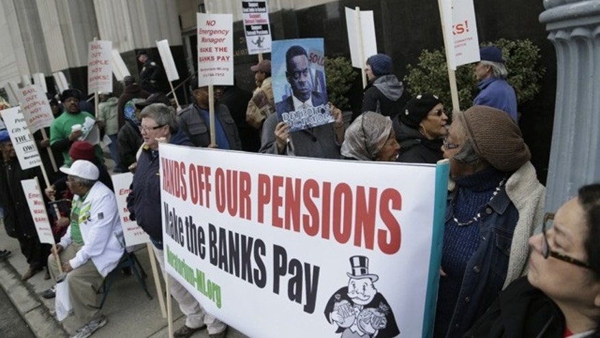 April 1, 2014: Protestors against deeper cuts in pensions march in front of the Theodore Levin Federal Courthouse in Detroit. (AP Photo/Detroit Free Press, Mandi Wright, File)