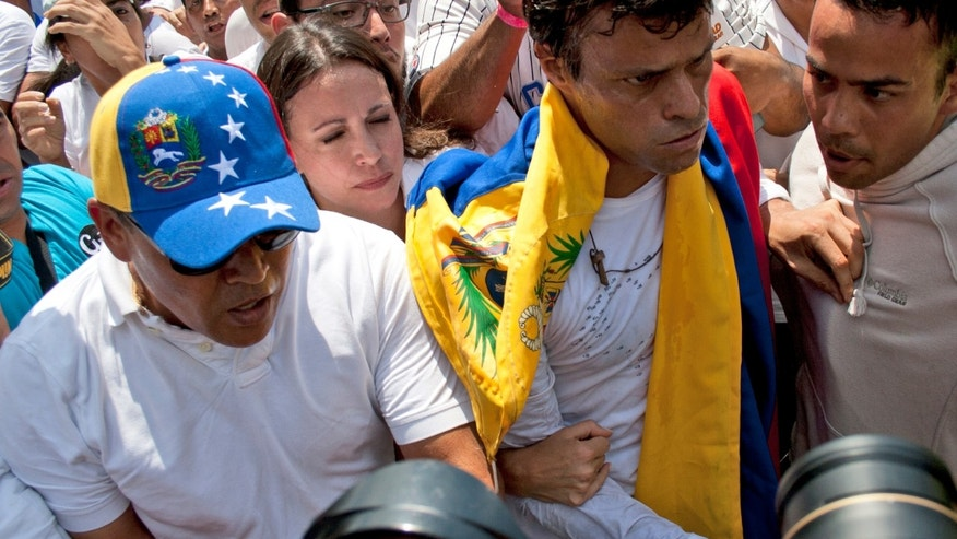 Draped in a Venezuelan national flag, opposition leader Leopoldo Lopez, second from right.