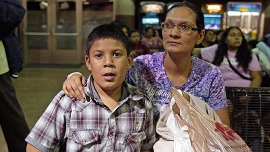 Maria Eva Casco, left, and her son Christian Casco of El Salvador, sit at at the Greyhound bus terminal, Thursday, May 29, 2014 in Phoenix. About 400 mostly Central American women and children caught crossing from Mexico into south Texas were flown to Arizona this weekend after border agents there ran out of space and resources.  Officials then dropped hundreds of them off at Phoenix and Tucson Greyhound stations, overwhelming the stations and humanitarian groups who were trying to help. (AP Photo/Rick Scuteri)