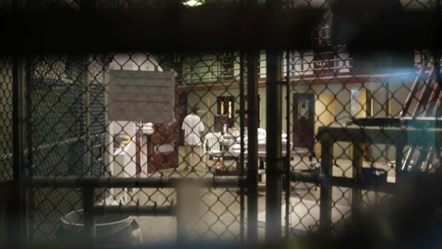 In this photo reviewed by a U.S. Department of Defense official, a prisoner walks through a communal pod inside an area of the Guantanamo Bay detention center known as Camp 6, an area for prisoners who are considered highly compliant with the rules, at Guantanamo Bay Naval Base, Cuba, Saturday, June 7, 2014. (AP Photo/Ben Fox)