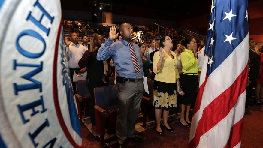 "Jean Naason, 39, of Haiti, left, recites the ""Oath of Allegiance"" during a naturalization ceremony administered by the U.S. Citizenship and Immigration Services (USCIS), Thursday, June 5, 2014, in Miami. Fifty candidates from various countries became U.S. citizens in celebration of the launch of the first annual Immigrant Heritage Month.  (AP Photo/Lynne Sladky)"