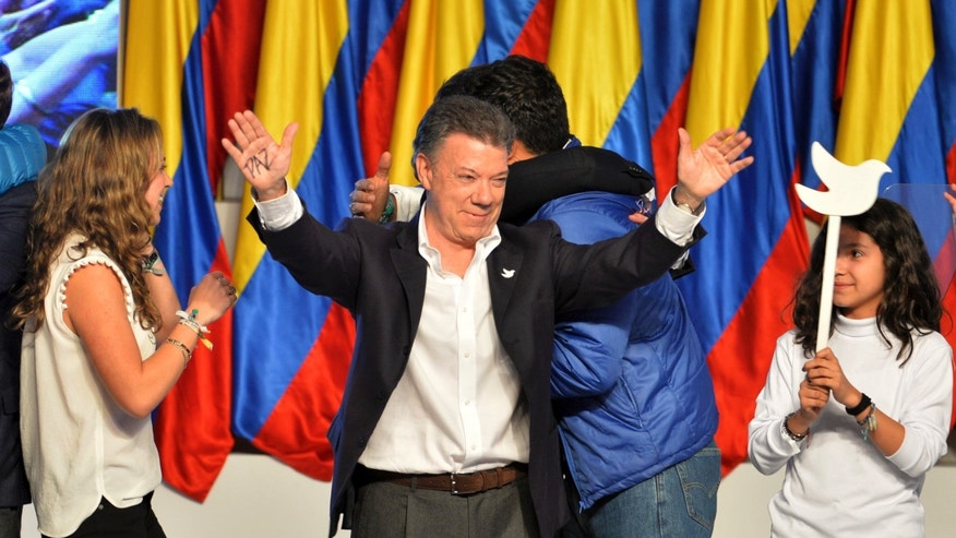 President Juan Manuel Santos celebrates his victory in the presidential runoff at his campaign headquarters in Bogota, Colombia, Sunday, June 15, 2014. Santos defeated challenger Oscar Ivan Zuluaga, of the Democratic Center, and won a second four-year term. (AP Photo/Santiago Cortez)