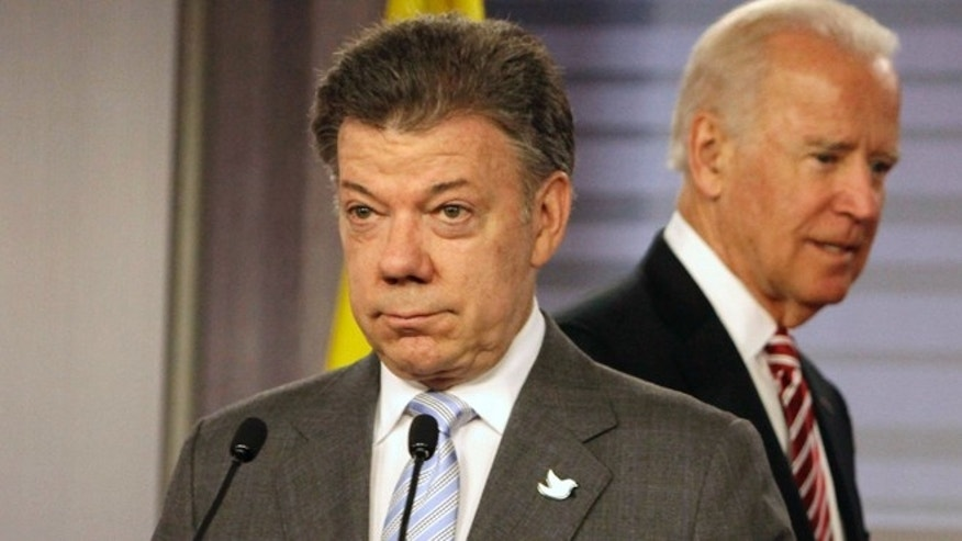 Colombia's President Juan Manuel Santos, front, and U.S. Vice President Joe Biden arrive to give a joint news conference at the presidential palace in Bogota, Colombia, Wednesday, June 18, 2014. Biden met with Santos just three days after the Colombian president won re-election in what was widely seen as an endorsement of talks to end the Western Hemisphere's last sizable armed conflict. (AP Photo/Javier Galeano)