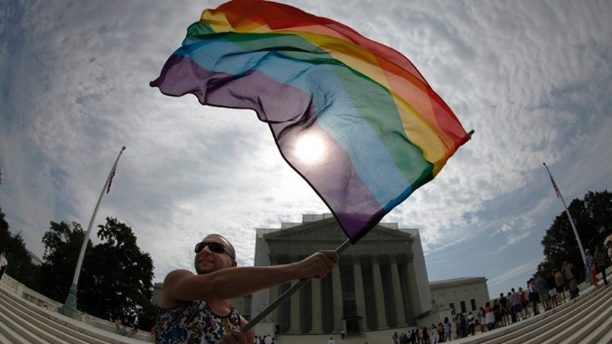 June 24, 2013: Gay marriage supporter Vin Testa waves a rainbow flag in anticipation of U.S. Supreme Court rulings in the cases against California's gay marriage ban known as Prop 8 and the 1996 federal Defense of Marriage Act (DOMA), outside the court building in Washington. (Reuters)