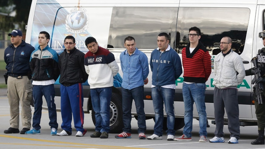 July 1, 2014: Police flank seven men accused of murdering a Drug Enforcement Administration agent, during a media presentation at the counter-narcotics base in Bogota, Colombia.