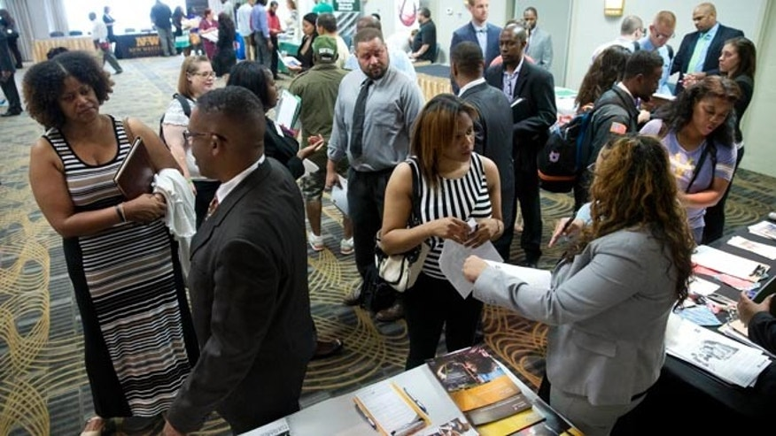 In this June 23, 2014 photo, job seekers and recruiters meet during a job fair in Philadelphia.