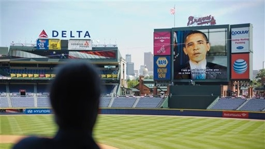 President Barack Obama addresses more than 1,000 new citizenship candidates in a taped message during a naturalization ceremony at Turner Field, home of the Atlanta Braves baseball team, Wednesday, July 2, 2014, in Atlanta. U.S. Citizenship and Immigration Services welcomed 1,094 new citizens from 81 countries as part of their annual Independence Day celebration marking the nations 238th birthday this year. (AP Photo/David Goldman)