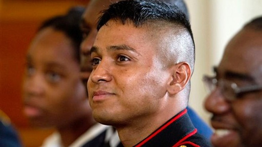 Marine Private First Class Oscar Gonzalez, who was born in Guatemala, listens as President Barack Obama speaks during a naturalization ceremony for active duty service members, including Gonzalez, and civilians, Friday, July 4, 2014, in the East Room of the White House in Washington. Obama highlighted a positive side of the immigration debate by presiding over an Independence Day citizenship ceremony for service members who signed up to defend the U.S. even though they weren't American citizens. (AP Photo/Jacquelyn Martin)